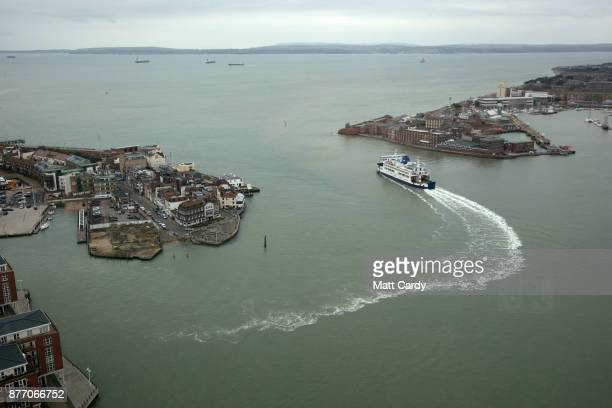 The Isle of Wight ferry leaves Portsmouth docks on November 21 2017 in Portsmouth England HMS Queen Elizabeth is the lead ship in the new Queen...