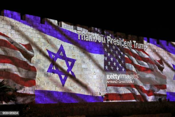 TOPSHOT The Israeli and United States flags are projected on the walls of the ramparts of Jerusalem's Old City to mark the opening of the new US...