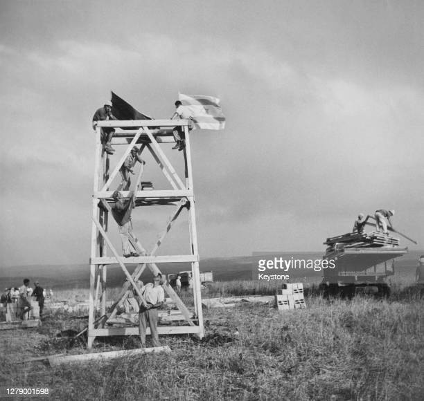 The Israeli flag flies from atop a wood-built structure, with people sitting on the structure as well as unloading lengths of wood and a roofing...