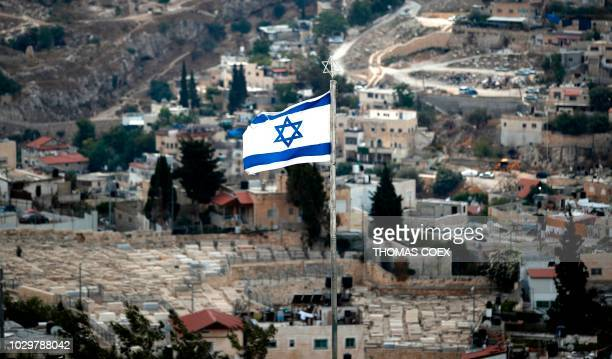 The Israeli flag flutters on the Mount of Olives with East Jerusalem arab neighbourhood of Silwan on the background near the Jerusalem's Old City on...