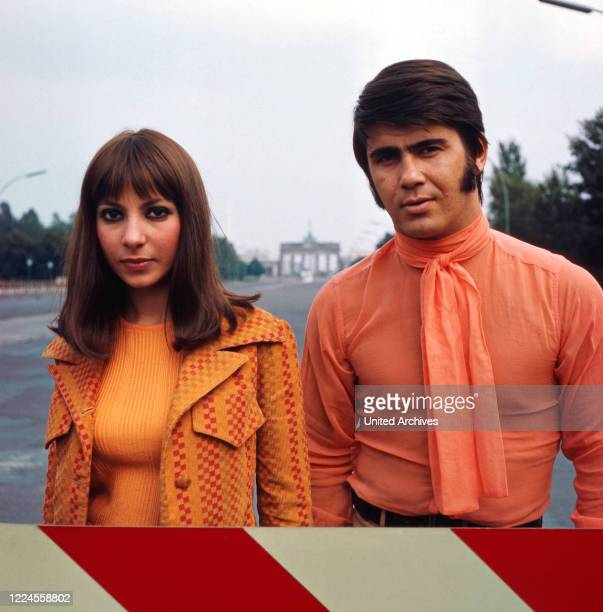 The Israeli musician couple Esther Abi Ofarim posing in orange clothes in front of the Brandenburg Gate Germany 1967