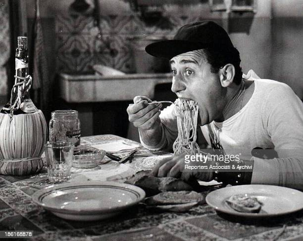The Italian actor Alberto Sordi sitting dowun at the table and eating spaghetti in the movie 'An American in Rome'. Rome, 1954.