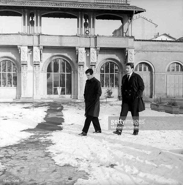 The Italian actor of cinema theatre and tv Corrado Pani and the US actor Joseph Walsh are walking on the snow in the courtyard of the seat of the...