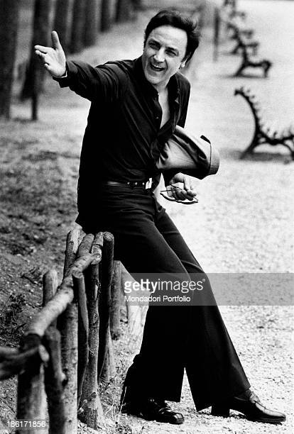 The Italian actor Paolo Carlini sitting on the wooden fence at the public gardens yelling for someone with a sweeping gesture of the hand great stage...