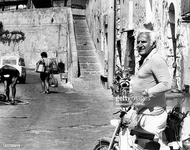 The Italian actor scriptwriter and director Adolfo Celi crossing the street with a moped Ponza 1970s