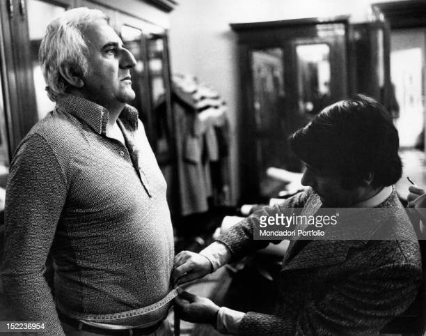 The italian actor scriptwriter and director Adolfo Celi getting his waist measured by a tailor Rome 1970s