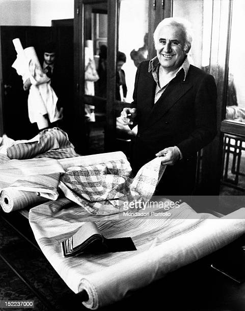 The italian actor scriptwriter and director Adolfo Celi holding a piece of fabric in his hand at the table of a dressmaker's shop Rome 1970s