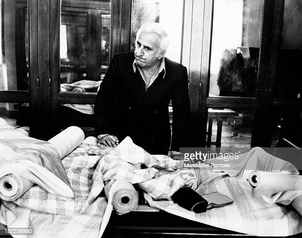 The italian actor scriptwriter and director Adolfo Celi leaning on the table of a dressmaker's shop piled with fabric Rome 1970s