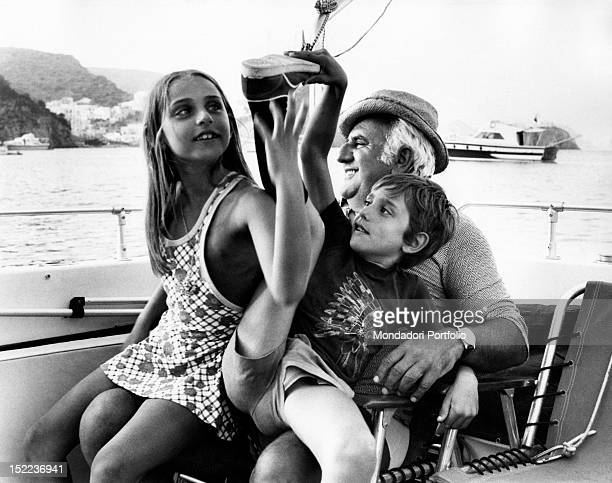 The italian actor scriptwriter and director Adolfo Celi on board a motorboat with his children Leonardo and Alessandra sitting on his knee Ponza 1970s