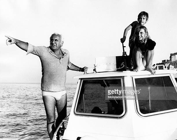 The Italian actor scriptwriter and director Adolfo Celi showing something to his children Alessandra and Leonardo Celi sitting on the deck of a...
