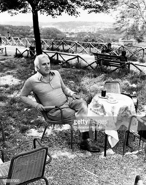 The italian actor scriptwriter and director Adolfo Celi sitting at a bar table outdoor Rome 1970s