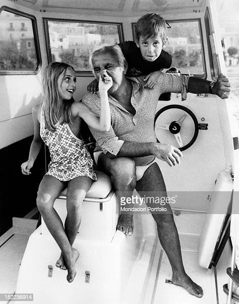 The Italian actor scriptwriter and director Adolfo Celi sitting in a motorboat playing with his children Alessandra and Leonardo Celi Ponza 1970s