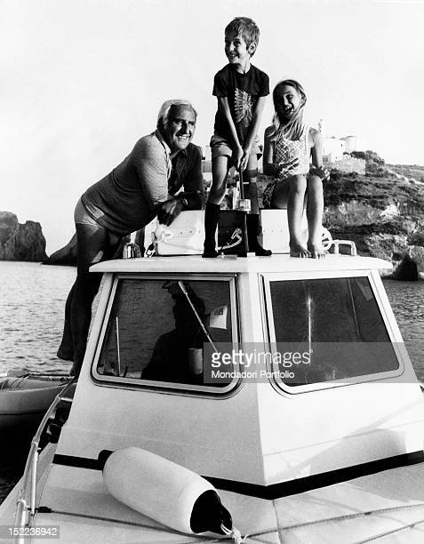 The italian actor scriptwriter and director Adolfo Celi smiling with his children Leonardo and Alessandra sitting in a motorboat Ponza 1970s