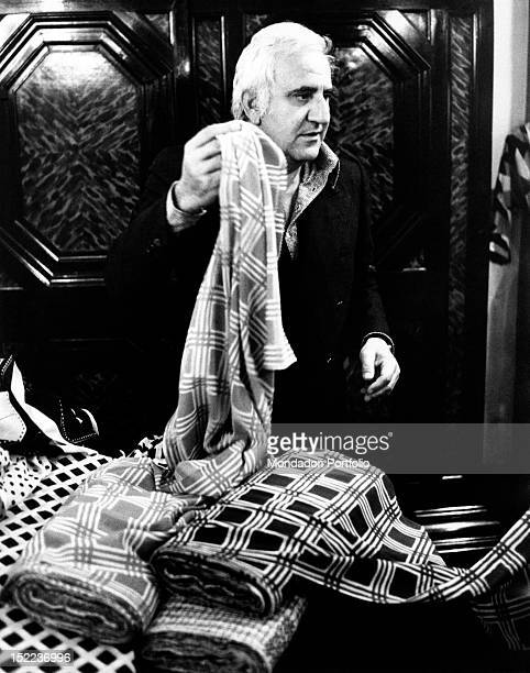 The italian actor scriptwriter and director Adolfo Celi taking a piece of fabric in his hand from the table of a dressmaker's shop Rome 1970s