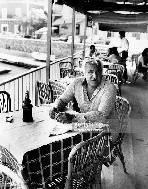 The italian actor scriptwriter and director Adolfo Celi waiting sitting at a table on the terrace of a restaurant Ponza 1970s