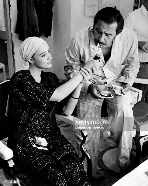 The Italian actress and director Eleonora Giorgi lighting a cigarette for the Italian actor and singer Domenico Modugno on the set of the film 'La...