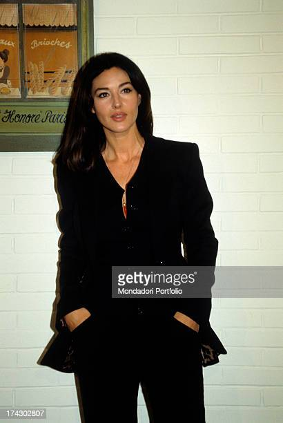 The Italian Actress and model Monica Bellucci poses with hands in her pockets acts naturally wearing a black suit