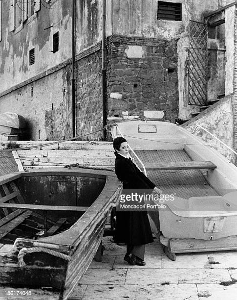 The Italian actress and singer Daniela Goggi in dark coat is standing between two rowboats by a small dock along the Tiber river she is the younger...