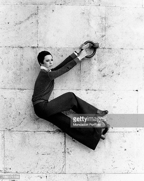 The Italian actress and singer Daniela Goggi in plastic pose hanging with her hands and feet at the mooring rings of a dock of the Tiber river the...