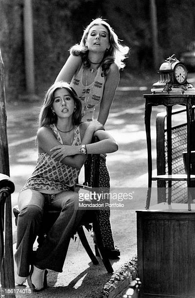The Italian actress and singer Daniela Goggi is posing next to her older sister singer actress and show girl Loretta next to some antique objects...