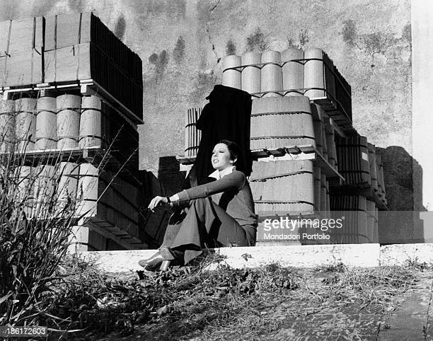 The Italian actress and singer Daniela Goggi is smiling while seated down with her arms on her knees on a sunny day in front of piles of building...