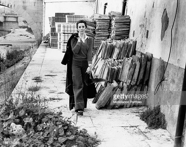 The Italian actress and singer Daniela Goggi is walking towards the photographer keeping her coat hanging on her back behind her some piles of...