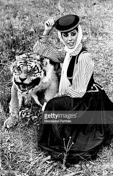 The Italian actress and singer Daniela Goggi seated on a lawn leaning her arm on a tiger peluche and wearing a traditional dress the artist reached...