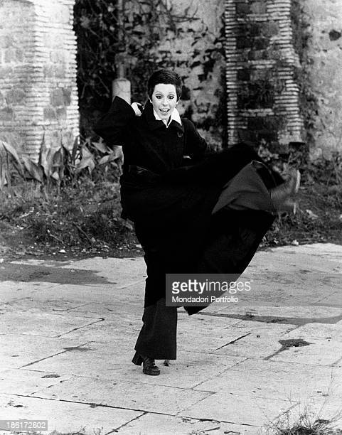 The Italian actress and singer Daniela Goggi wearing a dark coat dark trousers and heeled boots is improvising a dance movement the artist has...