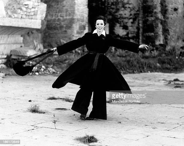 The Italian actress and singer Daniela Goggi wearing a dark coat dark trousers and heeled boots is improvising while smiling a pirouette the artist...