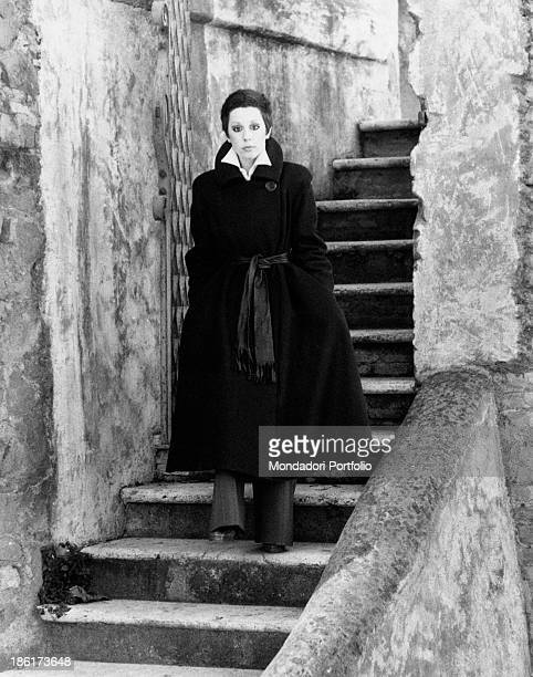 The Italian actress and singer Daniela Goggi wearing a dark coat is standing with absorbed expression on the stairs leading to a dock along the Tiber...