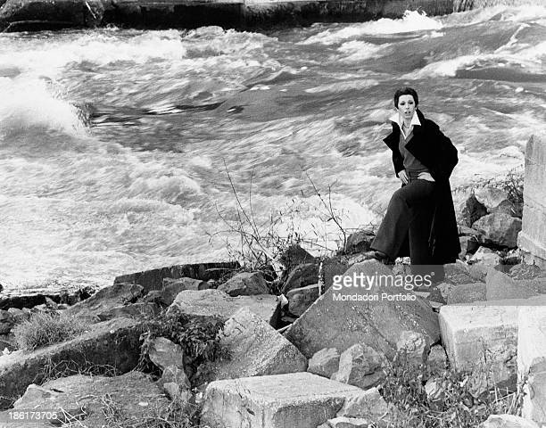 The Italian actress and singer Daniela Goggi wearing a dark coat is posing with hands on hips by a small dock next to the rushing waters of the Tiber...