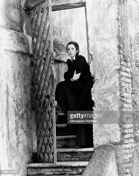 The Italian actress and singer Daniela Goggi wearing a dark coat is standing upright with a foot leaning on a gate with crossed arms and absorbed...