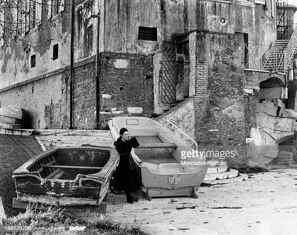 The Italian actress and singer Daniela Goggi wearing a dark coat between two rowboats by a small dock along the Tiber river she is the younger sister...
