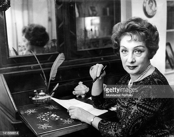 The Italian actress Andreina Pagnani writing a letter sitting on the desk 1970s