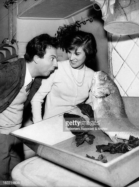 The Italian actress Antonella Lualdi in a fish shop showing a big fish to her husband the Italian actor Franco Interlenghi Rome 1950s