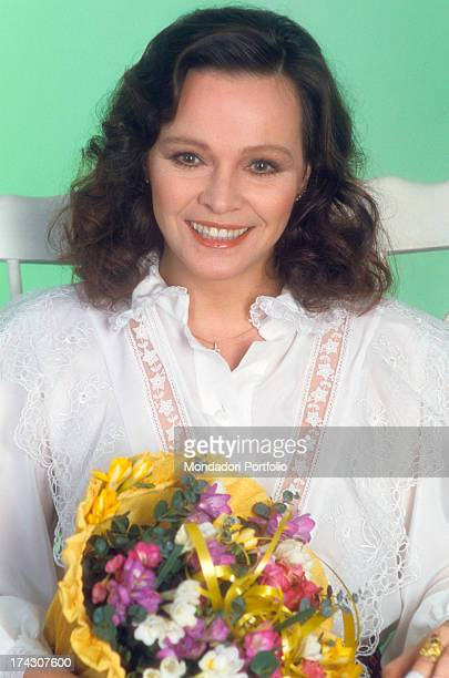 The Italian actress Laura Antonaz born Laura Antonelli is seated and smiling with a bucket of flowers in her hands the actress is wearing a white...