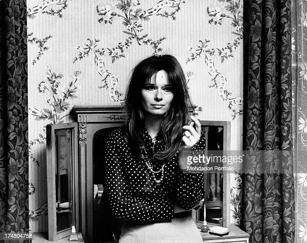 The Italian actress Lea Massari is posing in front of a dressing table in a flowers wallpapered room the actress looks absorbed in her thoughts and...