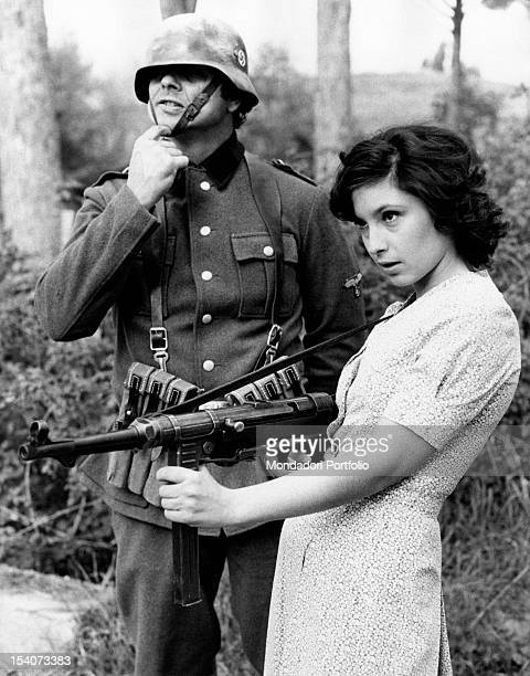 The Italian actress Lina Polito pretending to shoot with a machine gun during a break in the film Salvo D'Acquisto. Rome, 1975