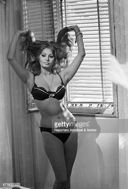 The Italian actress Loren Sophia as a prostitute undressing plaing with her long hair on the set of the film Yesterday today and tomorrow in the...