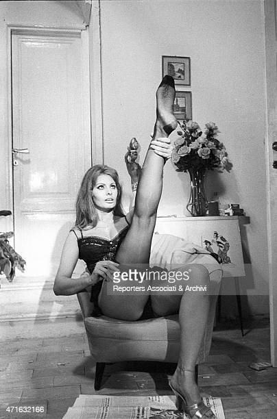 'The Italian actress Loren Sophia as a prostitute undressing taking off her nylon stockings while seating on an armchair on the set of the film...