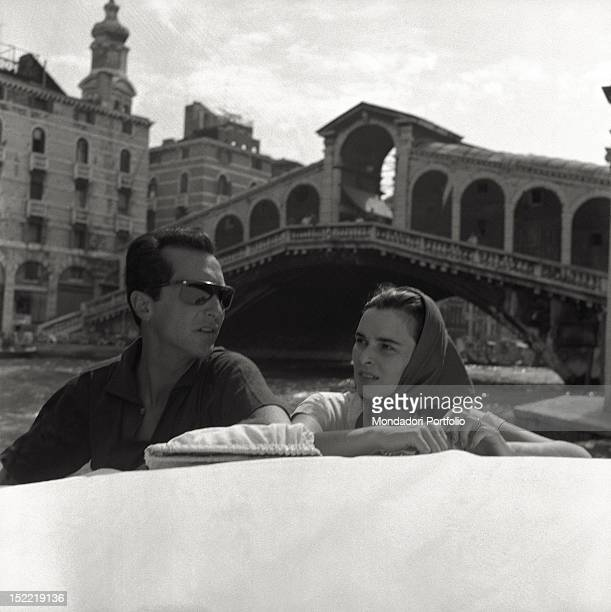 The Italian actress Lucia Bosè with her Spanish bullfighter husband Luis Miguel Dominguin on a boat in the vicinity of Rialto bridge. Venice, 1956.