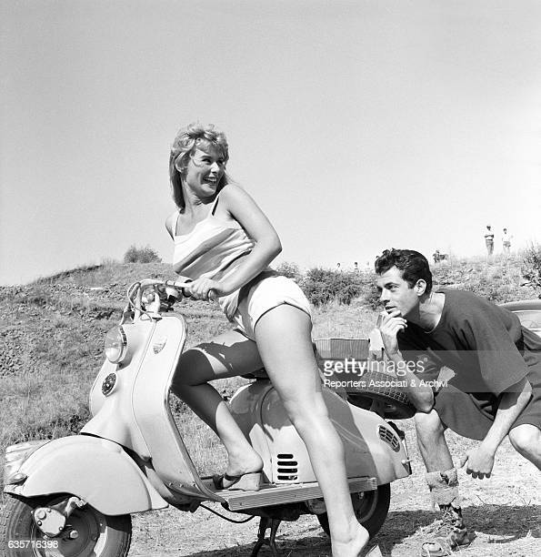 The Italian actress Marisa Allasio seated on a Vespa scooter on the set of the film 'The Sword and the Cross' jokes with the Spanish actor Jorge...