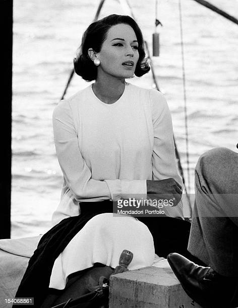 The Italian actress Silvana Mangano sitting by the shore of a basin of water in the film My Wife 1964