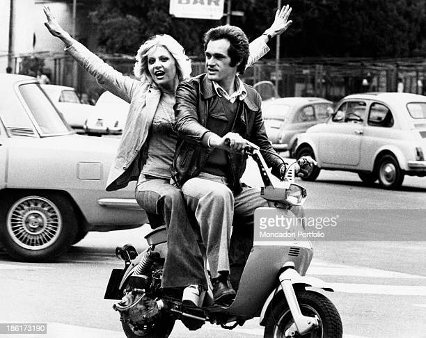 The Italian actress singer presenter Vanna Brosio seated on a motorcycle is exulting with raised arms next to the Italian actor and TV presenter Nino...