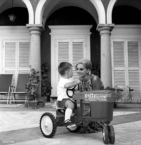 The Italian actress Virna Lisi born Virna Pieralisi is smiling while playing with her son Corrado who is driving his John Deere toy tractor Rome...