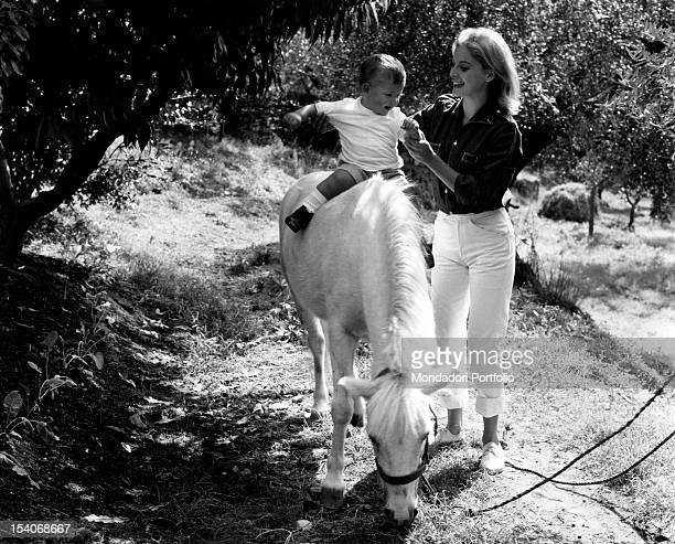 The Italian actress Virna Lisi taking her son Corrado Pesci pony riding They are in Villa Le Selve olive tree grove Marino 1963