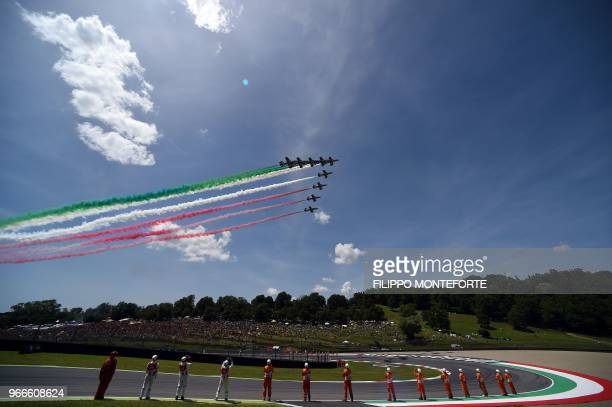 TOPSHOT The Italian Air Force aerobatic unit Frecce Tricolori spread smoke with the colors of the Italian flag prior the Moto GP Grand Prix at the...