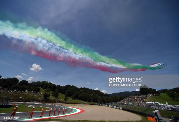 The Italian Air Force aerobatic unit Frecce Tricolori spread smoke with the colors of the Italian flag prior the Moto GP Grand Prix at the Mugello...