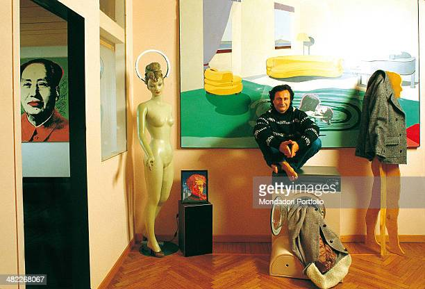 The Italian artist Silvio Pasotti sits with crossed legs on a washing machine from whose porthole spurts out a montgomery in a study rich of...
