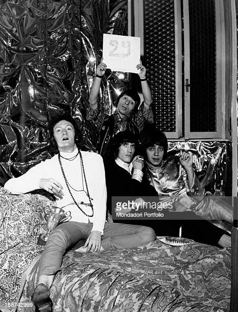 The Italian band Equipe 84 sitting on a bed Alfio Cantarella holds a sign saying 29 the other smoke a cigarette Italy 1968